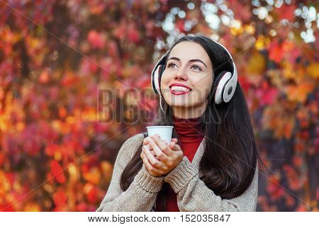 portrait of happy girl in colorful autumn park with takeaway coffee and headphones copy space. Beautiful young woman with music headphones holding a take away coffee cup and listening to the music.
