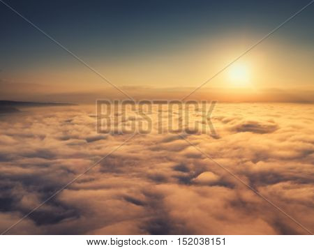 Flying above the clouds at sunrise. The Sun is rising up.