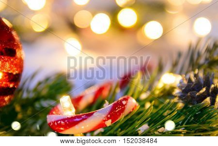 Christmas fir tree with lights and candy cane on snow in dark, view from above
