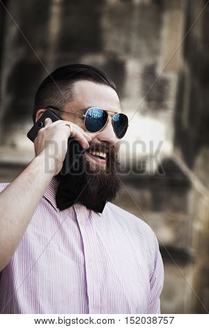 young hipster businessman with beard in sunglasses smiling and talking phone outdoors