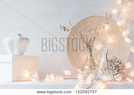 Christmas home decoration with burning lights on white wooden background.