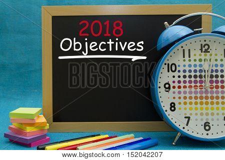 2018 New Year objectives written on a small blackboard.