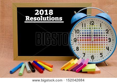 2018 New Year resolutions written on a small blackboard.