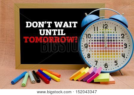 DON'T WAIT UNTIL TOMORROW message written on a small blackboard.
