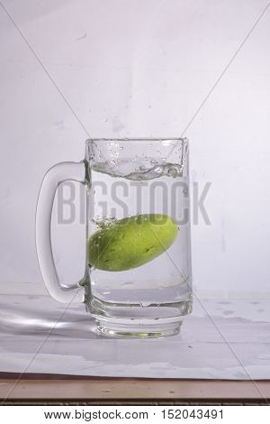 Water in glass with water splash on background