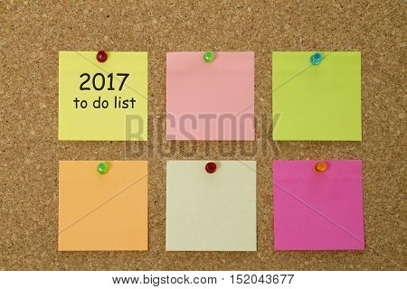 2017 New Year to do list on colorful sticky notes pinned on cork board.