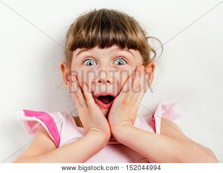 Surprised Small Girl on the White Wall Background