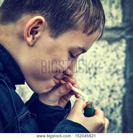 Toned Photo of the Kid smoke a Cigarette on the Street