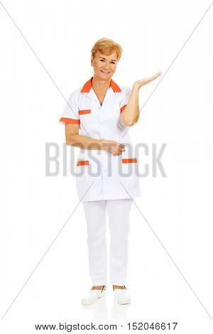 Smile elderly female doctor or nurse preseting something on open palm