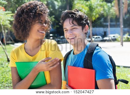 Latin female student talking with caucasian boyfriend outdoor in the city in the summer