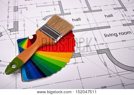 Building drawing on paper, paint brush and color samples, selecting paint colors, construction planning