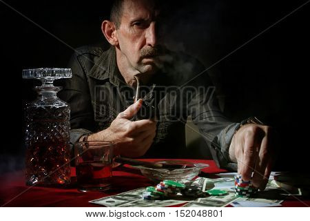 old man smoke pipe and play poker