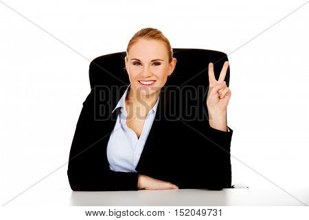 Happy business woman sitting behind the desk and shows victory sign