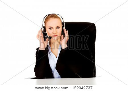 Phone operator in headphones sitting behind the desk