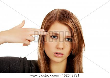 Teenage woman committing suicide with finger gun gesture