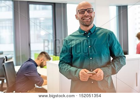 Portrait of confident mid adult businessman smiling with colleague in background at office