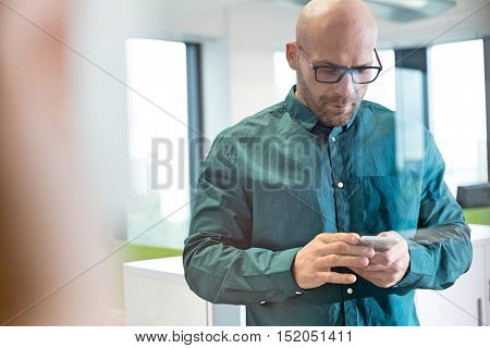 Mid adult businessman using mobile phone in office