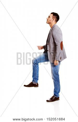 Side view of a businessman climbs the stairs
