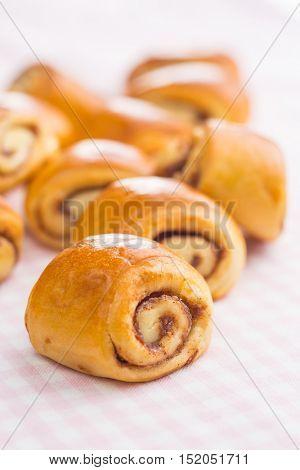 Mini cinnamon buns on pink checkered tablecloth.