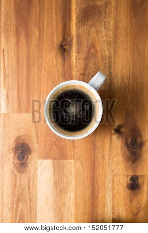 Cup of coffee on wooden table. Top view.