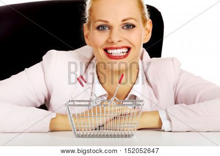 Smile business woman sitting behind the desk with small shopping basket