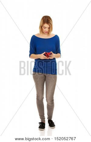 Young beautiful woman is looking into her empty wallet