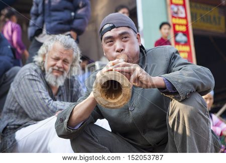 Bac Ha, Vietnam - Oct 17, 2015: Vietnamese civilian artist performing traditional melody with a wooden trumpet at a weekly flea market. Bac Ha along with Sapa are well known favorite destination.