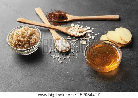 Natural ingredients for homemade scrub and wooden spoons on grey background