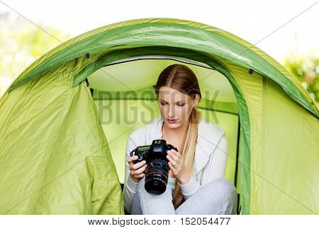 Young woman witho photo camera in a tent on the nature
