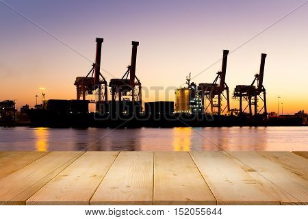 Silhouette of cargo freight ship and cargo container and crane at port for logistics and transportation background.