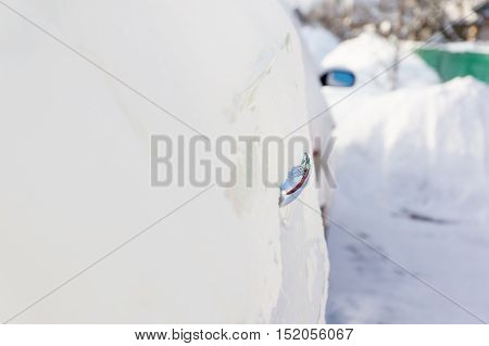 White car covered with snow during a blizzard