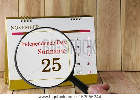 Magnifying glass in hand on calendar you can look Independence Day of Suriname on 25 November concept of a public relations campaign.