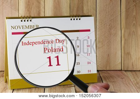 Magnifying glass in hand on calendar you can look Independence Day of Poland in 11 November concept of a public relations campaign.