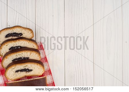 Bun with poppy seeds on a kitchen napkin and an old wooden table. Top view.