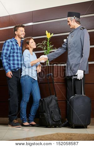 Concierge greeting young couple with luggage at hotel reception with a handshake