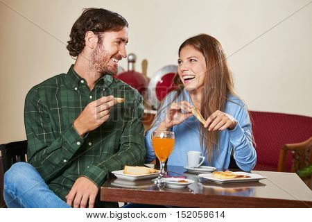 Happy couple eating breakfast in a hotel restaurant