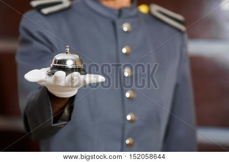 Hotel bell on hand of a hotel clerk at the reception