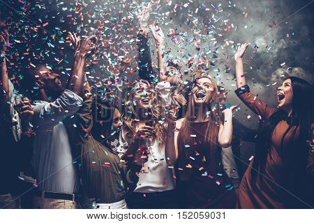 Unleashed fun. Group of beautiful young people throwing colorful confetti while dancing and looking happy