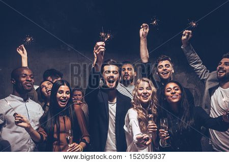 Party with friends. Group of cheerful young people carrying sparklers and champagne flutes