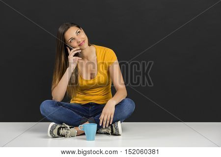 Beautiful woman sitting in the floor talking at phone