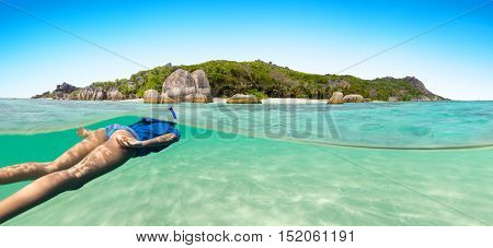 Young woman snorkling next to tropical island in shallow water