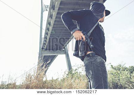 Gangster putting pistol into back pocket of jeans