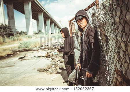 Vietnamese gangsters with pistols standing in ghetto
