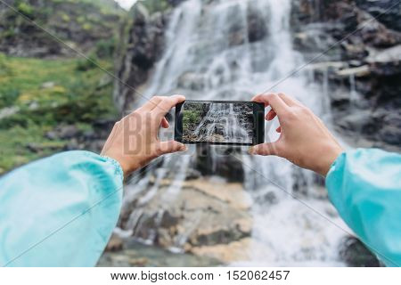 POV image of female traveler photographing with smartphone the waterfall outdoor