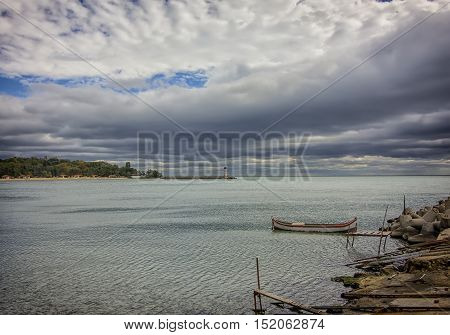 daily view of a fishing boat in the bay and the lighthouse
