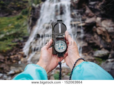 Female traveler searching direction with compass near the waterfall point of view shot