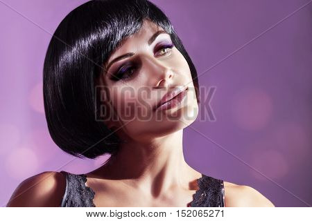 Portrait of a beautiful young woman over purple background, attractive model with gorgeous bob haircut and bright makeup, luxury fashion look