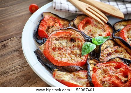 Tasty pizza topping, roasted aubergine with tomatoes and basil on the plate on the wooden table, delicious homemade food, Thanksgiving homemade food