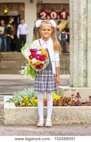 Grower Baby Girl First-grader With A Bouquet Of Flowers At The School