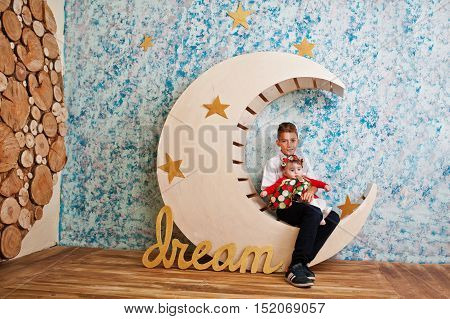 Little Brother With Baby Sister Sitting On Moon Decoration With Sign Dream